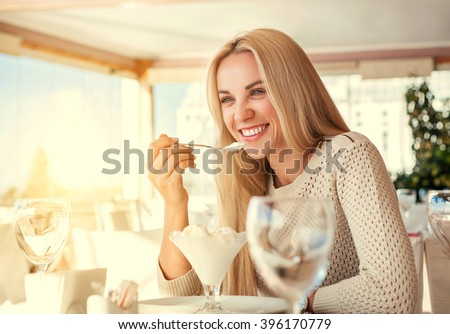 Positive young woman eating ice cream in light summer cafe - stock photo