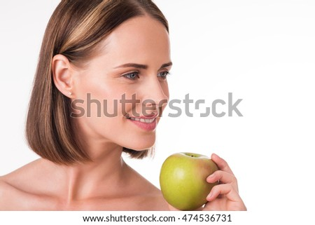 Positive young woman holding an apple