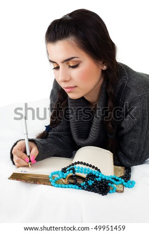 Positive young woman lay in bed and write down into dairy - stock photo