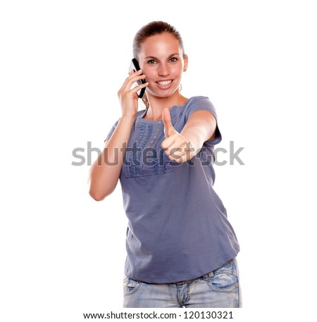 Positive young woman speaking on mobile phone standing over white background - stock photo