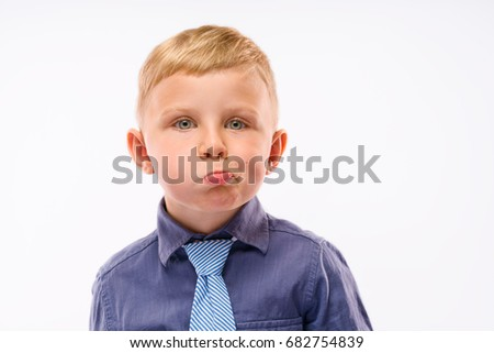 Positively Grimacing Baby Boss. Blond hair and bright eyes. Dressed in dark blue shirt with striped tie. Isolated background.