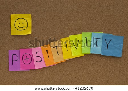 positivity concept on cork bulletin board - colorful sticky notes with a smiley - stock photo