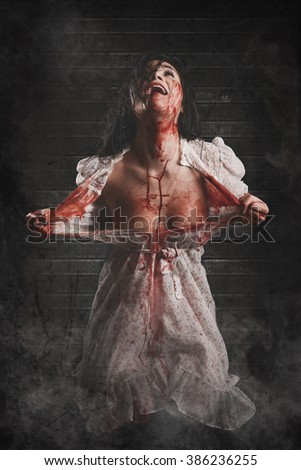 Possessed girl screaming with Bloody body - stock photo