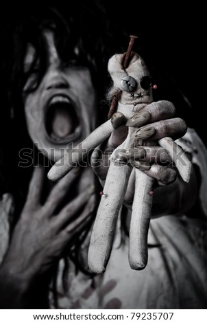 Possessed Woman Holding a Creepy Voodoo Doll - stock photo