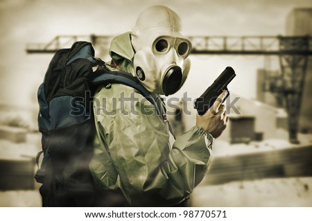 Post apocalypses world halloween concept. Portrait of man in gas mask with handgun - stock photo