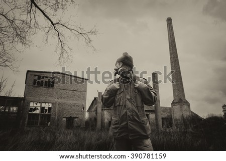 Post apocalyptic survivor in gas mask and backpack walking through devastated civilization. - stock photo
