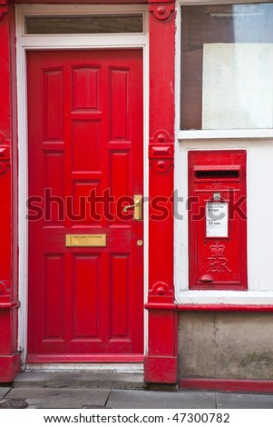 Post Box next to a red door - stock photo