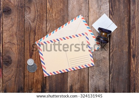 Post card with envelope and old stamp with coins on grunge wooden table still life - stock photo