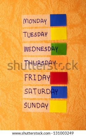 post it monday to sunday on orange background - stock photo