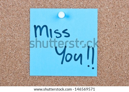 Post it note blue with miss you message on cork - stock photo