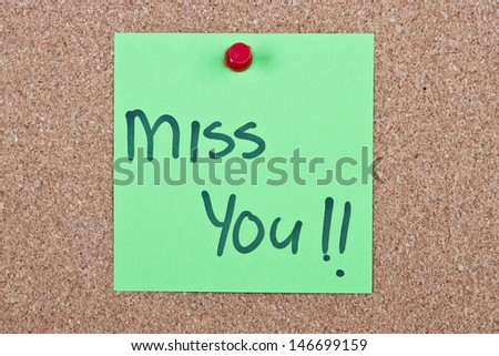 Post it note green with miss you message on cork - stock photo
