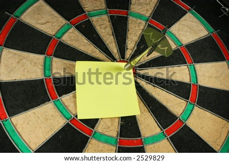 Post-It note on a dart board. Dart used as a push pin. - stock photo