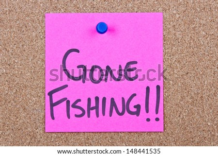 Post it note on wood in pink with gone fishing - stock photo