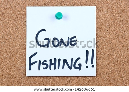 Post it note on wood in white with gone fishing - stock photo