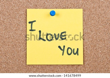 Post it note on wood in yellow with I love you - stock photo