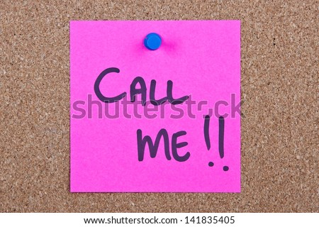 Post it note pink with call me message on cork