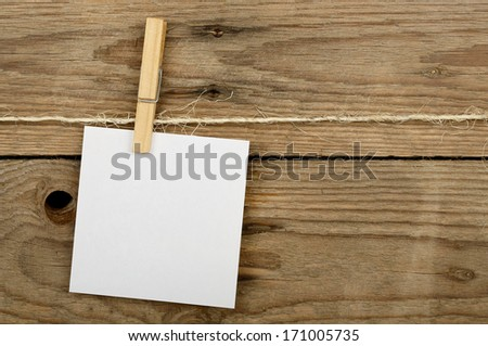 post it note with clothes peg against wooden surface - stock photo