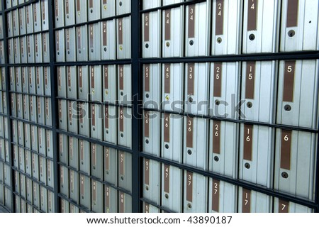 post office boxes letterboxes metal with brown numbers. uniform postboxes in line row organised pattern - stock photo
