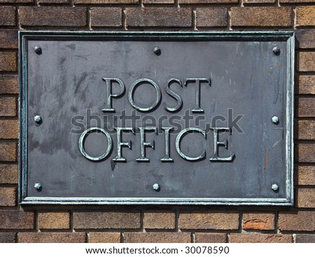 Post office sign made of brass and bolted on a brick wall