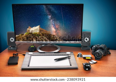Post production desk with digital camera, memory cards, graphic tablet, and monitor to advertise youself and your work. Monitor with stars photo. - stock photo