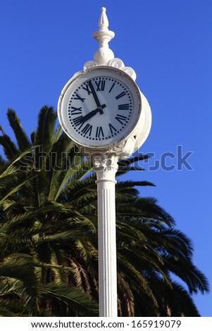 Post with big white clock Roman numerals - stock photo
