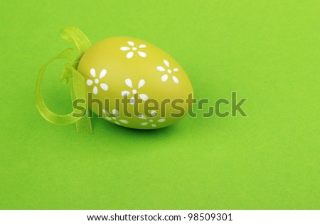 postcard as a green with small lovely white flowers painted egg on green background on Easter/painted egg - stock photo
