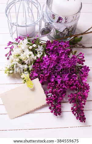 Postcard with fresh white and violet lilac flowers on white painted wooden planks. Selective focus. Place for text on empty tag.  - stock photo