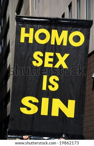 Poster claiming gay sex as sin, held up during a demonstration - stock photo
