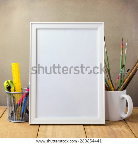 Poster mock up template with office items and painting brushes on wooden table - stock photo