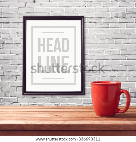 Poster mock up template with red cup on wooden table over brick white wall - stock photo