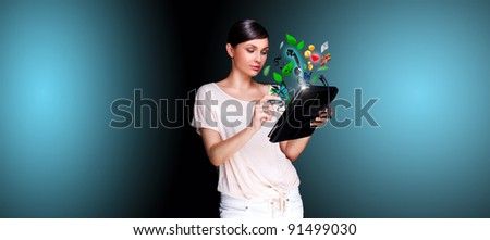 Poster portrait of young beautiful woman holding her universal device - tablet pc. Lots of things are appearing from the display. Universality of modern devices concept - stock photo