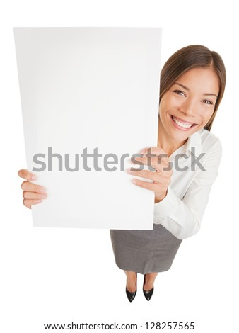 Poster sign woman holding up blank placard sign for your attention showing copyspace for advert or text. Fun high angle view of a happy young smiling professional woman isolated on white background - stock photo