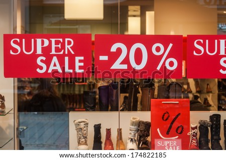 posting at a window display with cutting of prices - stock photo
