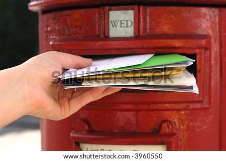 posting many letters to red british postbox on street - stock photo