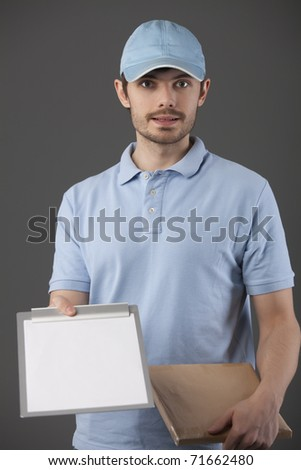 postman delivering a small package with clipboard for signature - stock photo