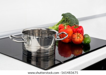 Pot and vegetables in modern kitchen with induction stove - stock photo