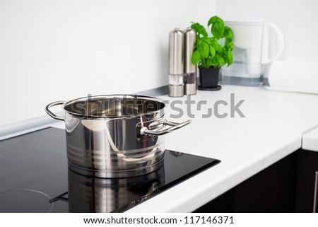 Pot in modern kitchen with induction stove - stock photo