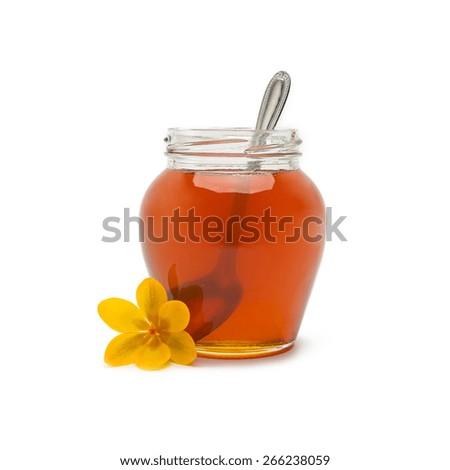 Pot of honey with spoon - stock photo