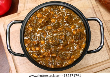 Pot of Indian Spinach Dal Cuisine on Table - stock photo