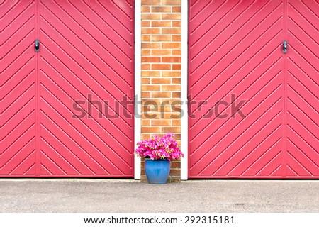 Pot of pink flowers in front of red garage doors - stock photo