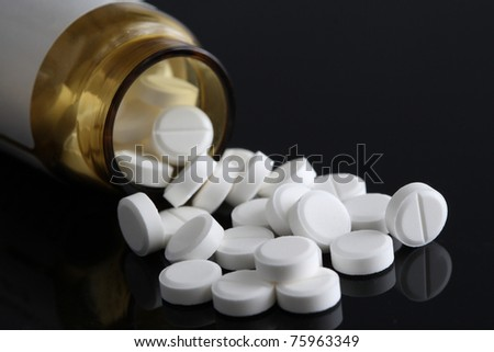 Pot of white tablets and their bottle - stock photo