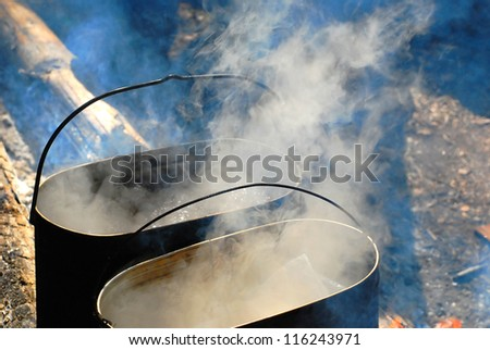 pot on the fire and smoke - stock photo