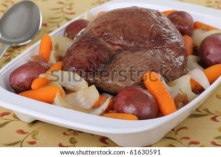 Pot roast with carrots, onions and potatoes in a serving plate - stock photo