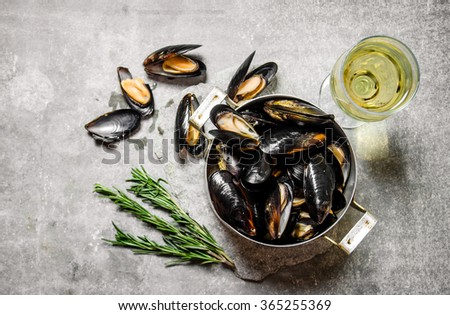 Pot with clams, rosemary and wine. On the stone table. Top view - stock photo