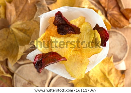 Potato and beet homemade chips in paper cone on natural wood background with autumn leaves. - stock photo