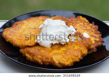 Potato and carrot pancakes with sour cream, close up - stock photo