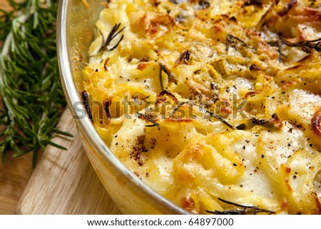 Potato and onion gratin, with rosemary. - stock photo