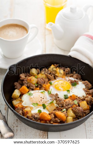 Potato and sweet potato hash with eggs in cast iron pan - stock photo