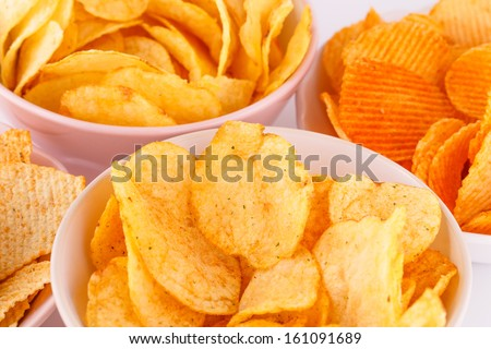 Potato and wheat chips in bowls on gray background. - stock photo