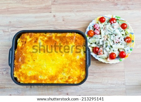 Potato casserole with eggs and meat. Fresh vegetable salad with sour cream - stock photo
